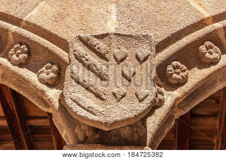 An architectural detail of the Verdugo palace in Avila, Spain. A coat of arms with stripes and hearts, toned photo