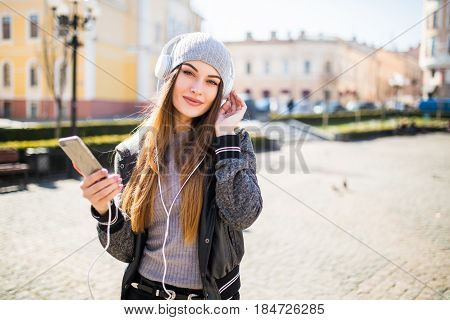 Young Beautiful Woman With Smart Phone Listening Music In The City