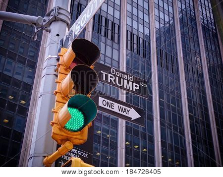 NEW YORK, JAN,20, 2017: NYC Wall street yellow traffic light black fake pointer guide One way green light to Donald Trump, 45th USA american president. USA politics policy