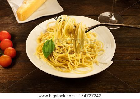 A photo of a fork with spaghetti with cherry tomatoes and a place for text, selective focus