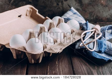 Wooden Whisk and Eggs on wooden kitchen table. Bake concept
