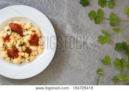 Gnocchi with tomato sauce on gray stone.Top view