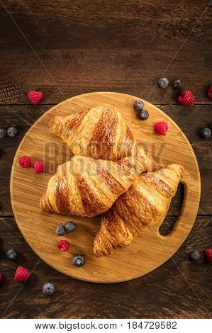 An overhead shot of crunchy French croissants with fresh raspberries and blueberries on a wooden cutting board with copy space