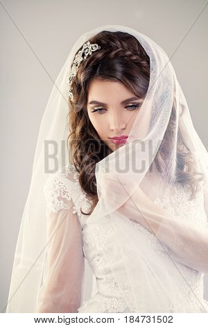 Beautiful Bride. Wedding Hairstyle and Make up. Closeup Portrait of Young Gorgeous Bride. Wedding. Studio shot. Beautiful Fiancee with Veil over her Face