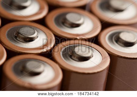 low angle closeup of electric batteries and accumulators AAA AA with selective focus on top