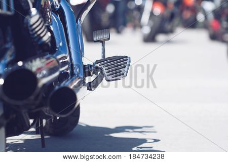 rear view of classical motorcycle pair of exhaust chrome pipes and foot holder selective focus