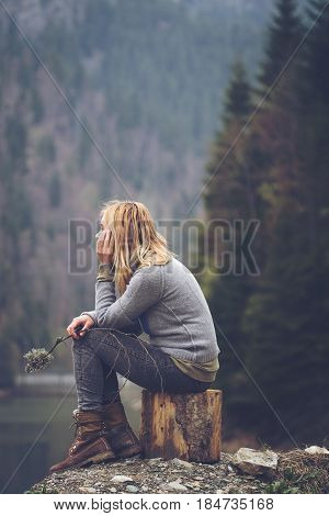 vertical side view portrait of Caucasian young blonde woman with light colored sweater and jeans holding a tree branch and meditating relaxing alone on a tree stump in front of a lake surrounded by forest mountains copyspace