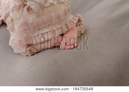 On a bed in lace a small bare foot of a baby