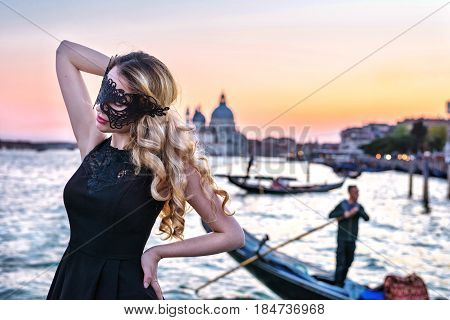 Portrait of a woman with a mysterious look at sunset in Venice. Girl wearing black mask and a gondola on Grand Canal background, Italy