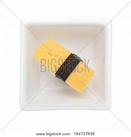 Sushi - Tamagoyaki nigiri in a square bowl isolated on white background