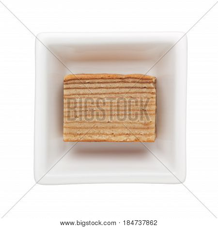 Slice of Kek lapis in a square bowl isolated on white background