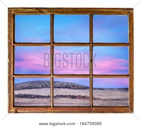 colorful sunset sky over Colorado foothills as seen through vintage, grunge, sash window with dirty glass