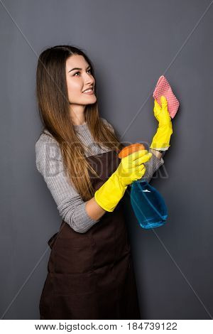 Young Woman Use Spray While Cleaning Up House Posing For Camera On Grey Background