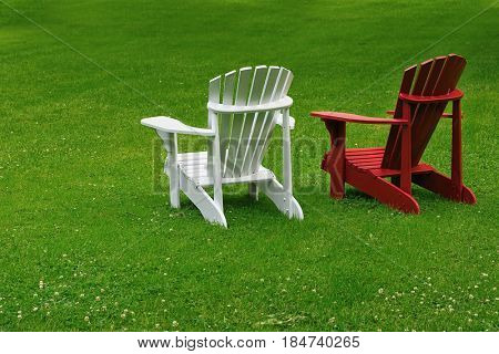 Red and white Adirondack chairs on a extensive lawn.