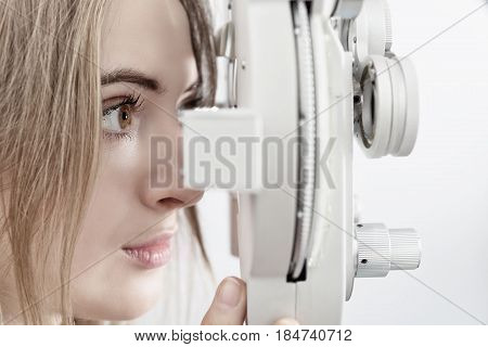 Woman Waiting For Eye Examination With Phoropter