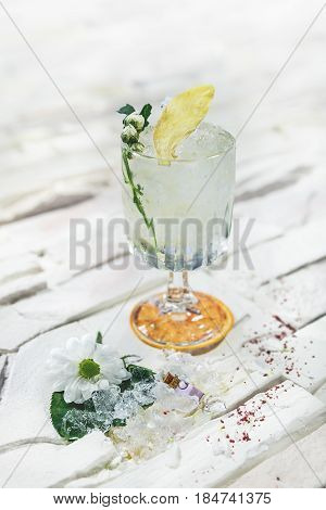 Bright alcohol cocktail with ginger garnish with ice, and flower on white background