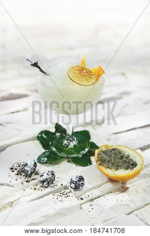 Bright yellow alcohol cocktail garnished with Passion fruit on white background