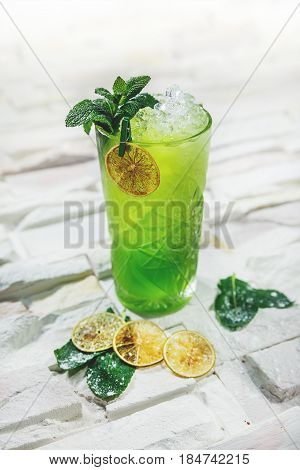 Bright green lemonade cocktail garnished with lemon and mint on white background