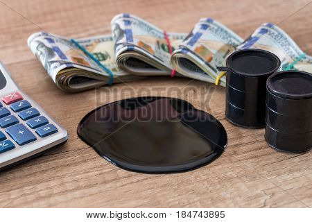Black Barrel With Oil Lies On Dollar Banknotes With Calculator On Desk. Sale Of Oil. Oil