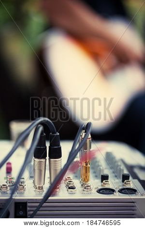 Cables connected to audio amplifier and an unrecognizable guitarist in the back. Shallow depth of field