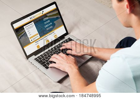 Man looking for home in a real estate website with a laptop, while sitting at home.