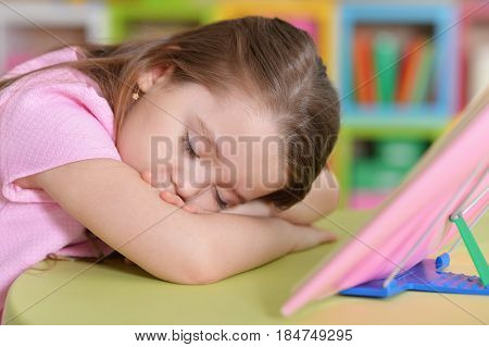 Little girl fell asleep at the table reading a book