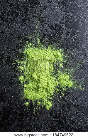Green matcha tea powder on black table.