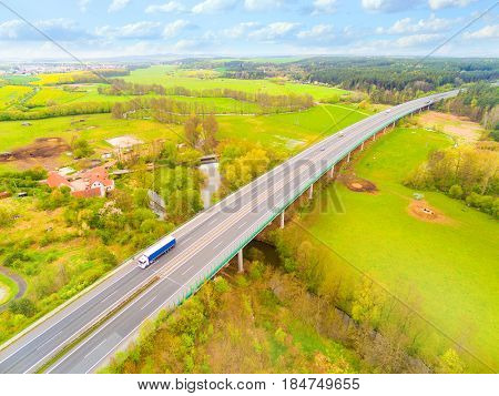 Aerial view of bridge over Radbuza River and green pastures. Highway D5 with traffic near Pilsen, Czech republic, Central Europe. Transportation and sustainable development concept.