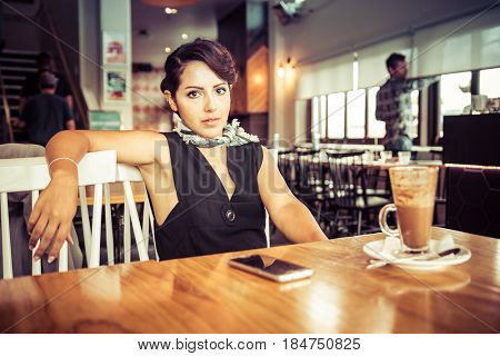 Woman relaxing in cafe with coffee drink