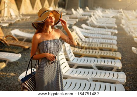 Relaxing woman enjoying the summer sun happy standing in a wide sun hat at the beach with face raised to the sunlight. Portrait of pretty caucasian girl on vacation with chaise-longue on background.