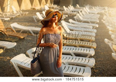 Relaxing woman with sunglusses on enjoying the summer sun happy standing in a wide sun hat at the beach with face raised to the sunlight. Portrait of pretty caucasian girl on vacation with chaise-longue on background.