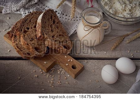 Fresh dairy products. Milk cottage cheese sour cream multigrain homemade bread fresh eggs and wheat on rustic wooden background. Organic farming dairy concept.