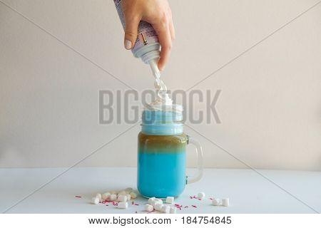 Girl is adding cream in cup of colored blue milk. Milk shake cocktaill frappuccino. Unicorn coffee unicorn food.
