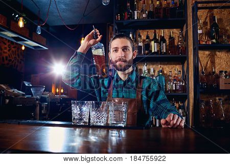 Barman bartender with a bottle of alcohol behind the counter in  bar.