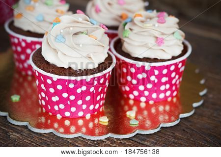 Chocolate cupcake with chocolate mousse cream icing on grunge dark wooden background