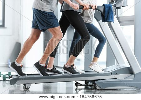 Family workout on treadmill side view in gym