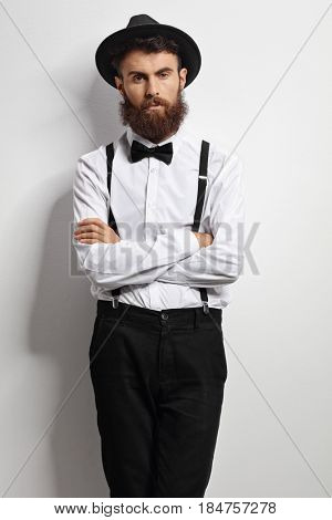 Bearded man with a bow tie and suspenders leaning against a white wall