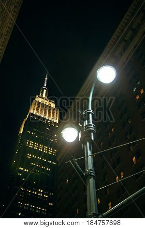 NEW YORK CITY -JUNE 21: View of Empire State building at night behind of city street lamp light, on March 21, 2016 in Manhattan, New York City, USA.
