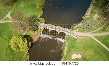 Aerial drone view of a quaint road bridge over an English river passing over a small weir.