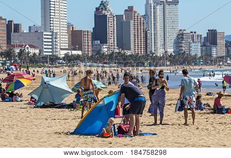 People On Visit To Beach Against Durban City Skyline