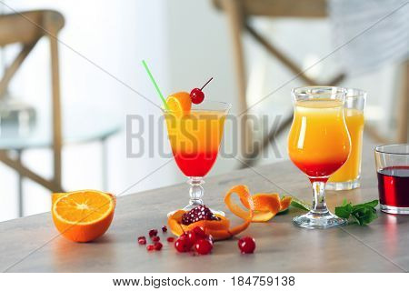 Glasses of Tequila Sunrise cocktail with ingredients on table