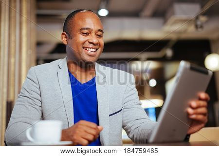 Image Of Happy Young African Man Using Digital Tablet In Cafe