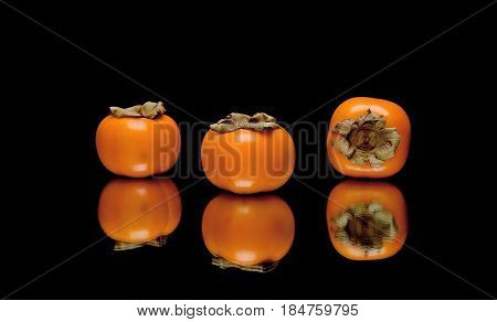 persimmon on a black background with reflection. horizontal photo.
