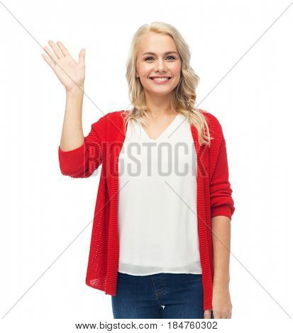 gesture, fashion, portrait and people concept - happy smiling young woman in red cardigan waving hand over white