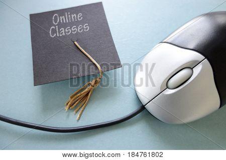 Closeup of a computer mouse and Online Classes graduation cap