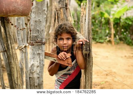 LA MULA SANTIAGO DE CUBA CUBA - NOVEMBER 27: Portrait of the Cuban girl in one of poorer provinces based for primitive enclosing its household in the mountains Sierra Maestra on Cuba La Mula in November 27 2016