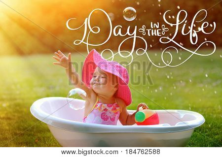little girl bathes in a bath with soap bubbles and text Day in the life. Calligraphy lettering vintage hand draw.