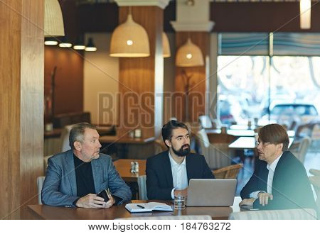 Profile view of confident middle-aged manager in eyeglasses presenting his ideas concerning joint project to male colleagues, they listening to him with interest while gathered together in cafe