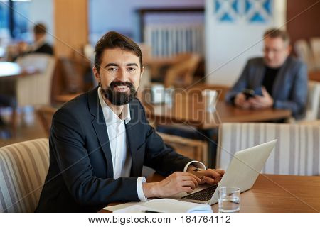 Smiling middle-aged financial manager with bushy beard looking at camera while sitting in lovely cafe and making corrections in annual accounting reports, waist-up portrait
