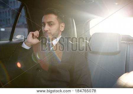 Sunlit portrait of handsome Middle-Eastern businessman speaking by phone on backseat inside expensive car and looking at camera